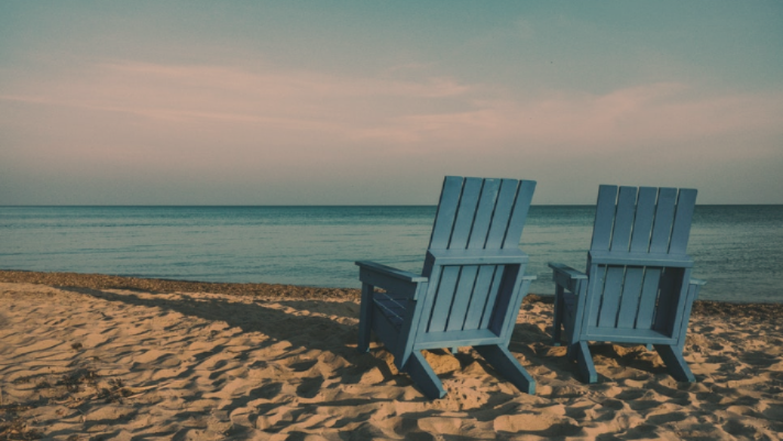 two blue chairs on a beach retirement
