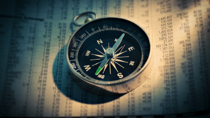 compass on a stock market performance paper