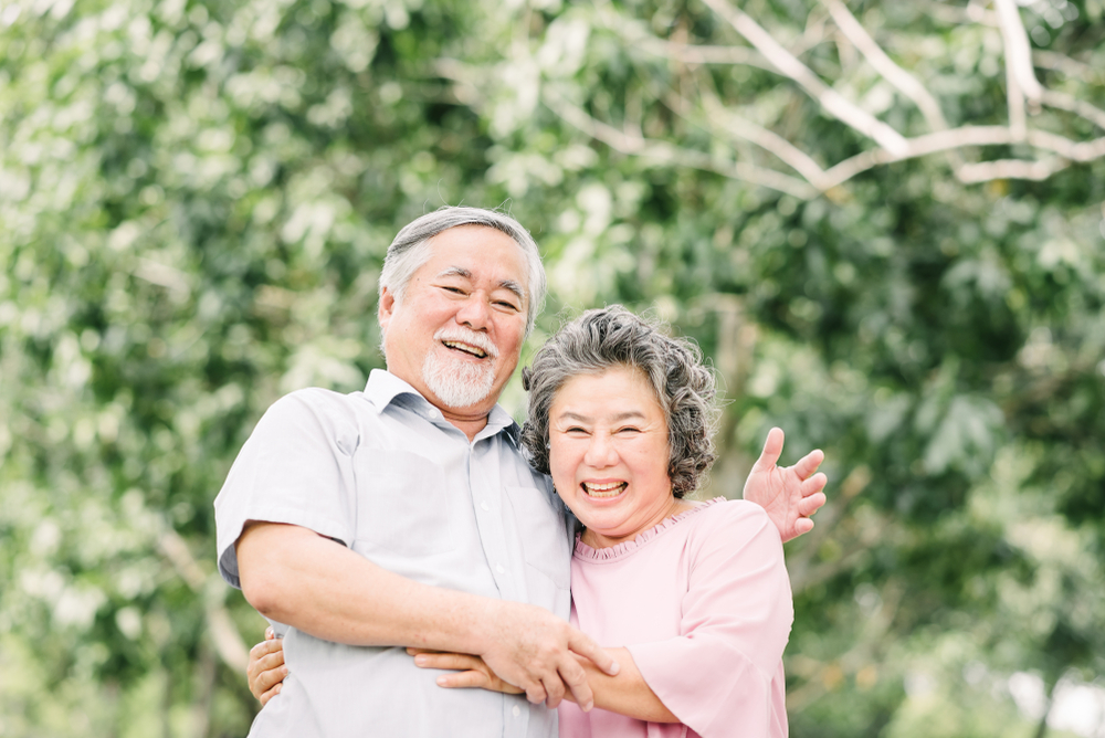 senior asian couple smiling while embracing each other life insurance