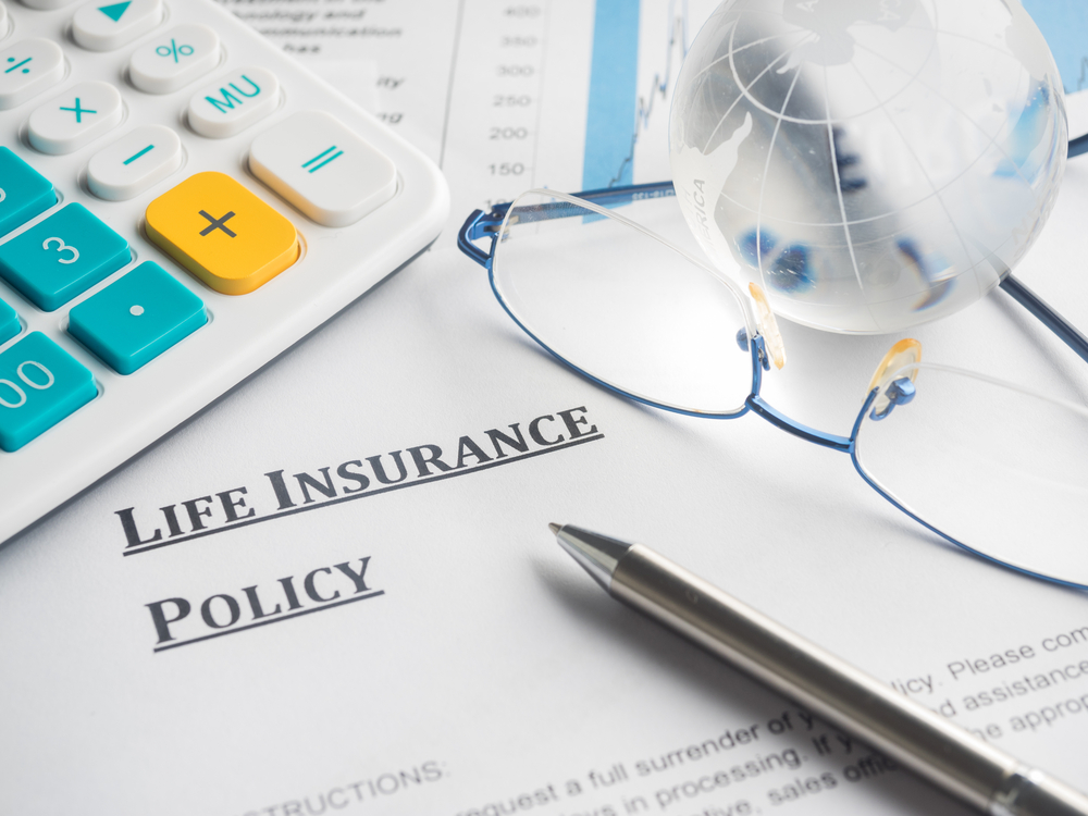 life insurance policy with glasses, calculator, and pen