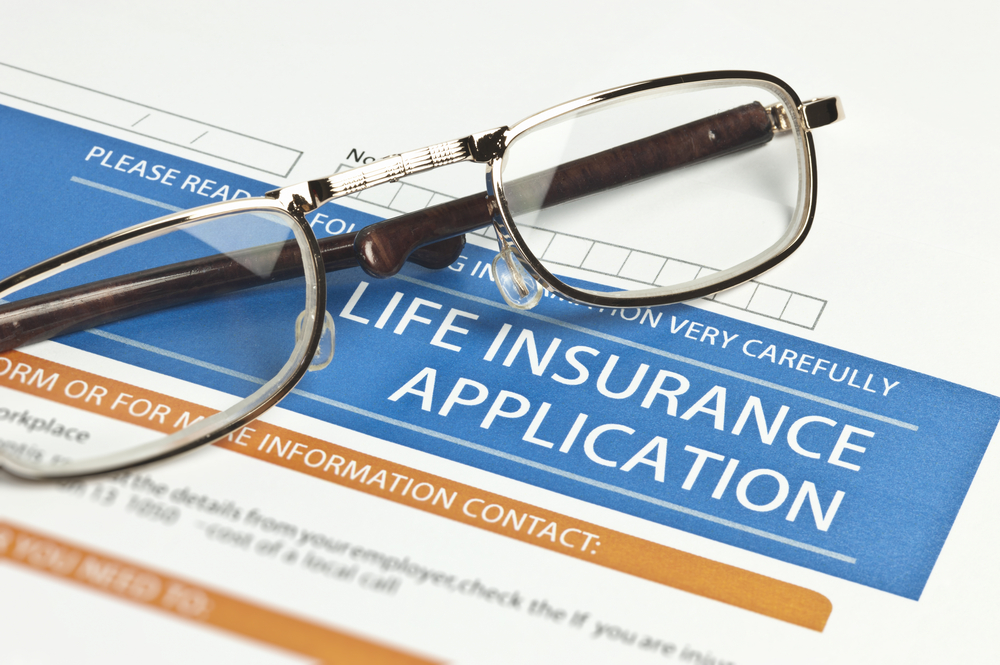 life insurance application for IUL with pair of glasses laying over the application