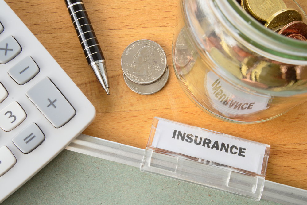 life insurance folder with calculator, pen, and change beside it