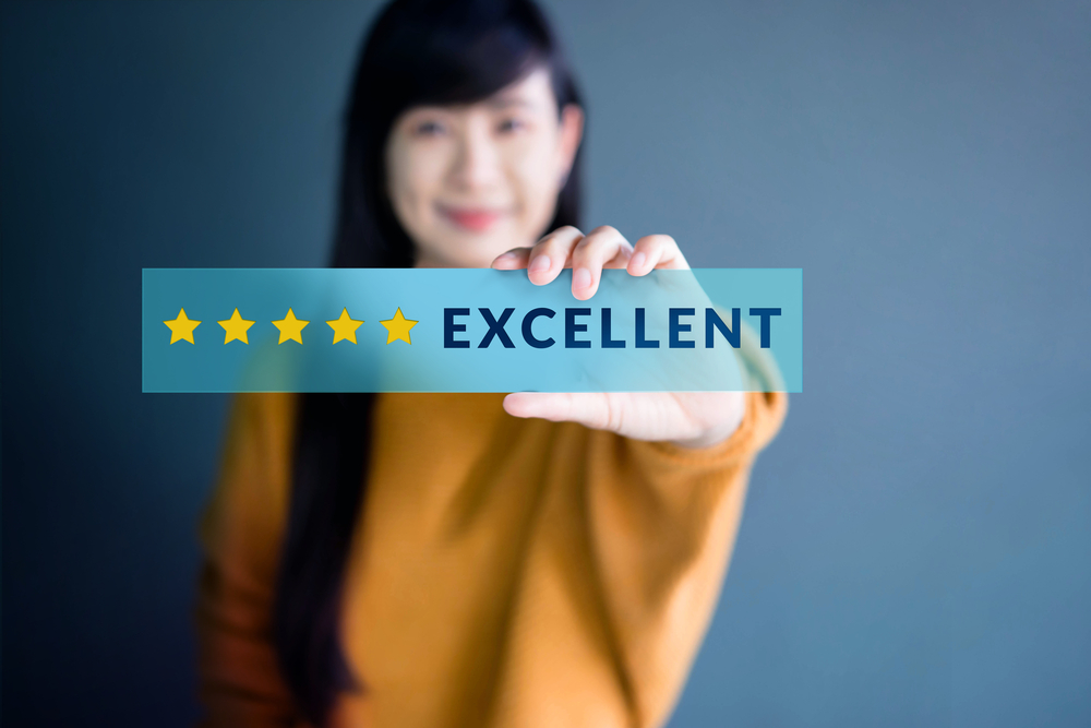 client holding up her 5-star review of financial advisor