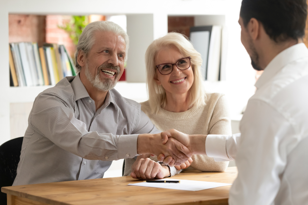 clients shaking hands with financial professional after buying long-term care insurance