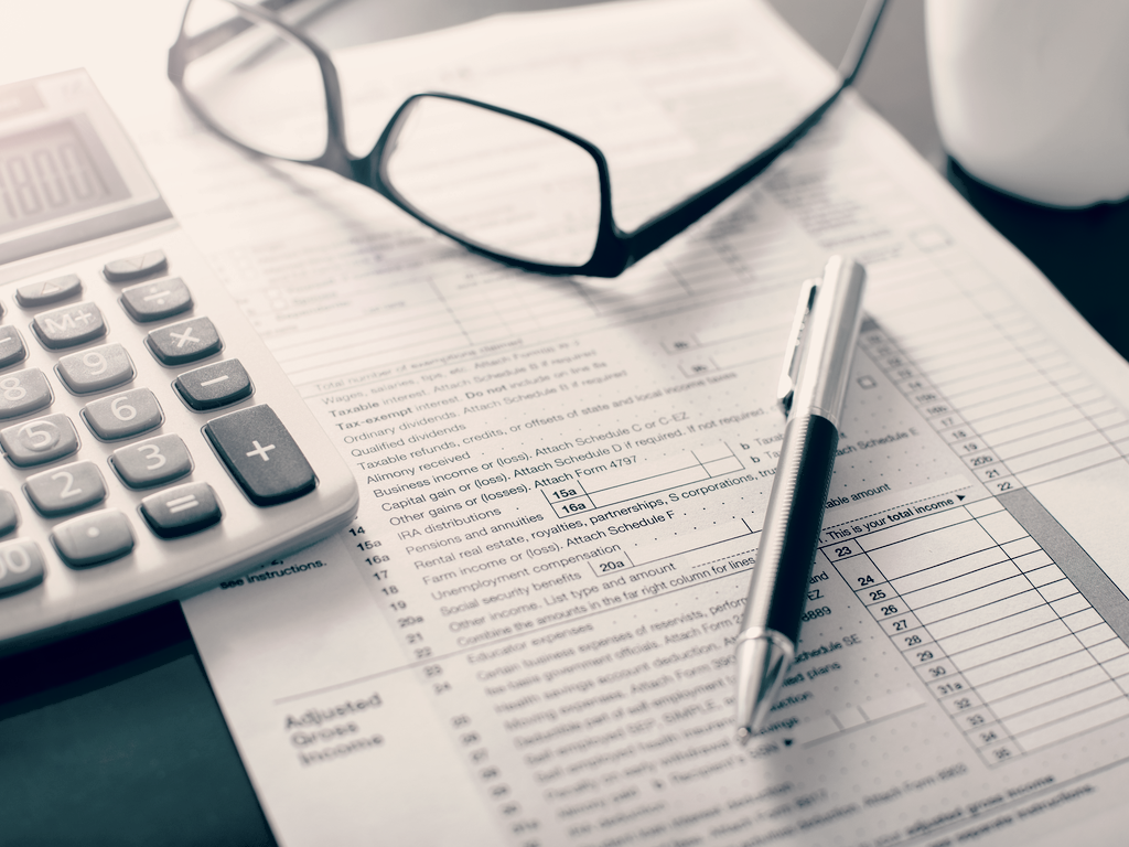 1040 tax form with calculator pen and glasses nearby