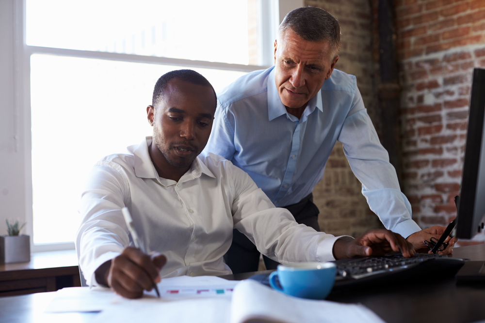 Financial professional mentoring younger financial professional for succession planning
