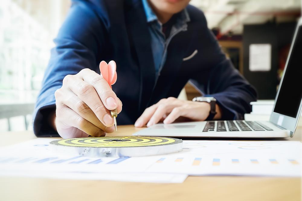 financial advisor hitting marketing goals with dart
