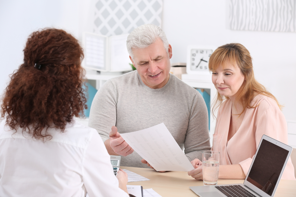 middle-aged couple speaking to their financial advisor about life insurance policies